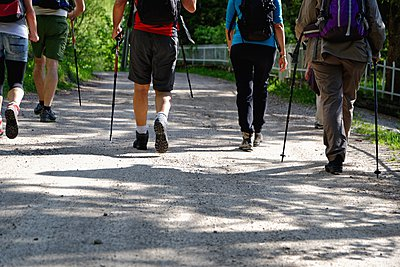 Rear waist down view of mature hikers on rural road, Grigna, Lecco, Lombardy, Italy - p429m1046882f by Costantino Costa