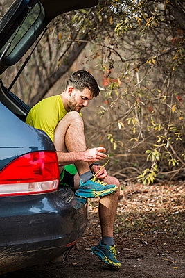 Runner tying shoelace in car trunk - p429m2075468 by JFCreatives