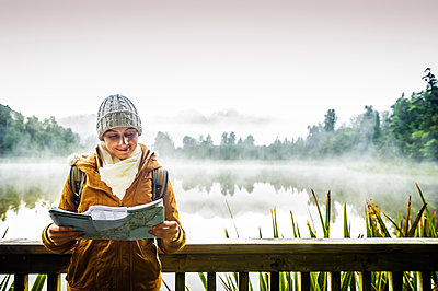 Hispanic woman wearing coat reading map at foggy mountain lake - p555m1304957 by Dave and Les Jacobs