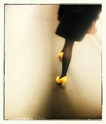 Woman dressed in black with yellow court shoes - p567m1095628 by Alexis Bastin