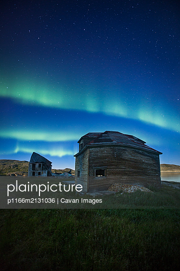 Aurora over abandoned buildings, Torngat Mountains - p1166m2131036 by Cavan Images