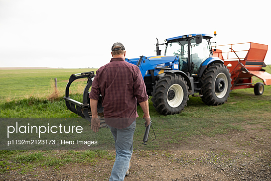 Male farmer walking toward tractor - p1192m2123173 by Hero Images
