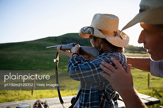 Man teaching woman how to fire a gun - p1192m2129352 by Hero Images
