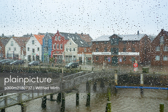 Germany, Schleswig-Holstein, Husum, Canal bridge and waterfront houses seen through window glass covered in raindrops - p300m2180737 by Wilfried Wirth