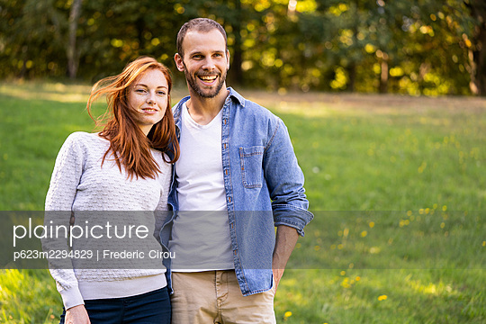 Portrait of smiling young couple enjoying a stroll in a park - p623m2294829 by Frederic Cirou