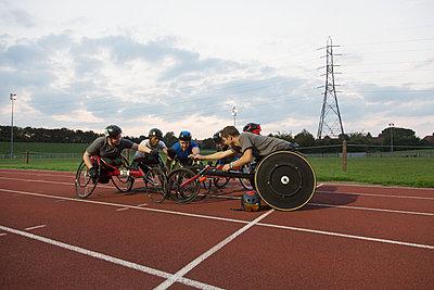 Paraplegic athletes huddling on sports track, training for wheelchair race - p1023m2067517 by Martin Barraud
