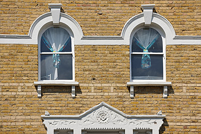 Two Victorian windows with curtains - p1048m2001824 by Mark Wagner