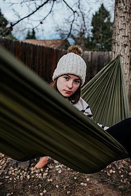 vertical portrait of preteen girl looking over hammock - p1166m2201316 by Cavan Images
