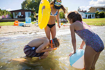 Brother and sisters playing in sunny summer lake - p1192m1183785 by Hero Images