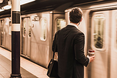 Young businessman waiting at metro station platform, holding disposable cup - p300m1192371 by Uwe Umstätter