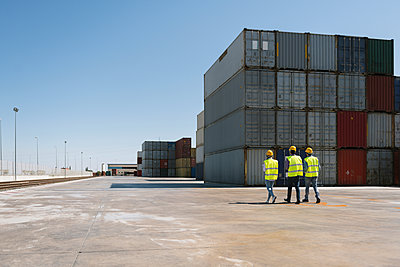Workers walking together near stack of cargo containers on industrial site - p300m2102342 von Hernandez and Sorokina