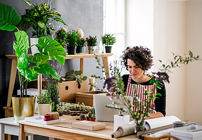 Young woman using laptop in a small shop with plants - p300m2143999 von HalfPoint