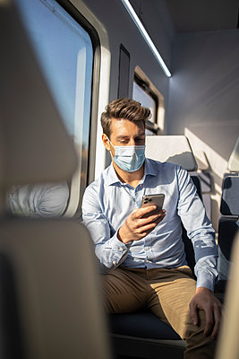 Businessman with protective face mask using mobile phone while sitting in train during COVID-19 - p300m2242883 by Ignacio Ferrándiz Roig