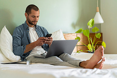 Young man using smart phone while sitting with laptop on bed at home - p300m2268098 by Steve Brookland
