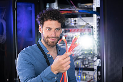 Male IT specialist looking at patch cord cables in server room - p300m2274582 by Florian Küttler