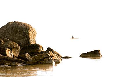 Man fishing in canoe on Lake Sebago, Maine in the dawn light - p3436444f by Gabe Palacio