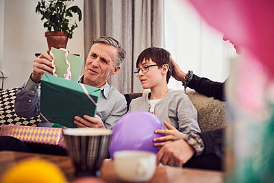 Boy and grandfather looking at greeting card and birthday present while sitting on sofa - p426m1580241 by Maskot