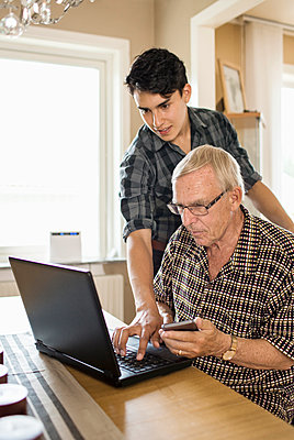 Grandson assisting grandfather in using laptop at home - p426m958734f by Maskot