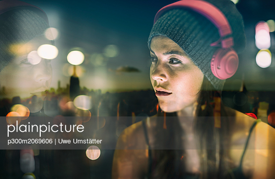 Portrait of young woman with headphones at twilight - p300m2069606 by Uwe Umstätter