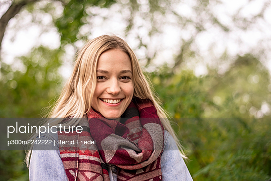 Blond woman with scarf in park during autumn - p300m2242222 by Bernd Friedel