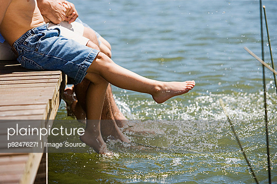 Father and sons splashing in lake - p9247627f by Image Source
