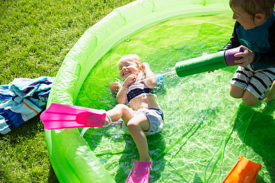 Playful brother spraying sister with squirt gun in sunny wading pool - p1192m1184002 by Hero Images