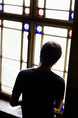 Mann blickt aus einem Fenster - p1316m1160389 von Peter von Felbert