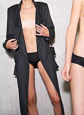 Zwei Frauen Körper halbnackt vor einer Beton Wand - p1504m2022686 von Jenny Bewer