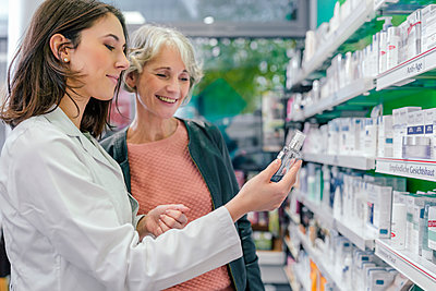 Pharmacist advising customer with cosmetics in pharmacy - p300m1550066 by Mareen Fischinger