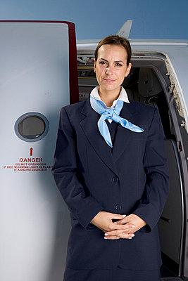 A flight attendant standing in front of a plane door - p3018314f by Halfdark