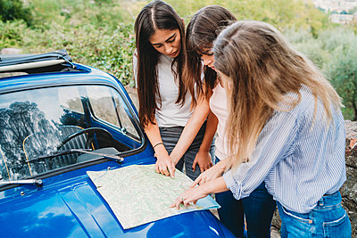 Friends reading route map on car bonnet in countryside - p429m2097518 by Lorenzo Antonucci