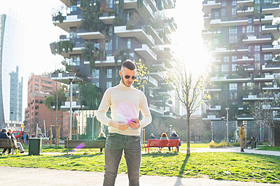 Young man using smartphone in city, Milano, Lombardia, Italy - p429m2127768 by Francesco Buttitta