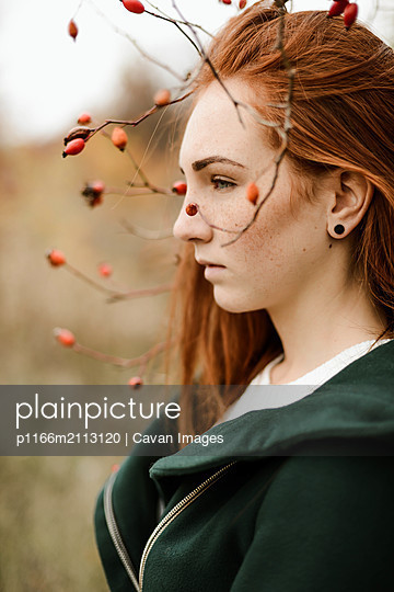 Thoughtful teenage girl with red head standing amidst plants - p1166m2113120 by Cavan Images
