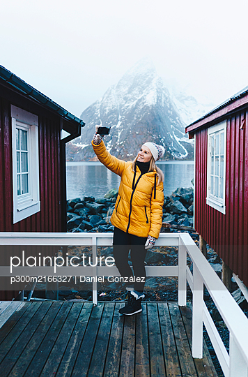 Tourist taking a selfie on a porch at Hamnoy, Lofoten, Norway - p300m2166327 by Daniel González