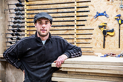 Man wearing flat cap standing next to a stack of wooden boards, looking at camera, tools in the background. - p1100m1575748 by Mint Images