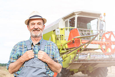 Confident farmer in front of combine harvester - p300m1188796 by Milton Brown