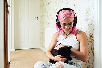 Happy young woman with black cat listening to music at home - p300m1494794 by Ivan Gener Garcia