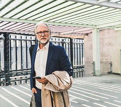 Serious mature businessman in the city looking around - p300m1587974 by Uwe Umstätter