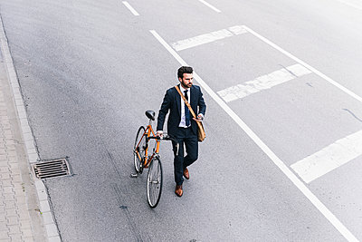 Businessman with bicycle and cell phone walking on the street - p300m2005331 by Uwe Umstätter