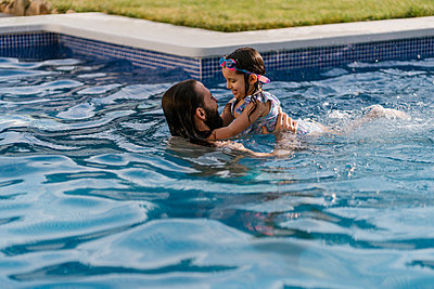 Father and little daughter spending time together in swimming pool - p300m2202579 by Ezequiel Giménez