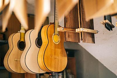 Guitars hanging in a line at workshop - p300m2220582 by Daniel González