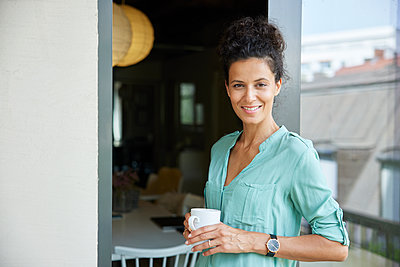 Smiling female professional holding coffee cup while leaning on door - p300m2293773 by Rainer Berg