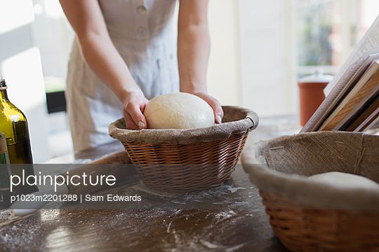 Woman placing dough into proofing basket in kitchen - p1023m2201288 by Sam Edwards