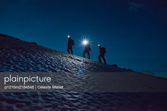 Mountaineers with headlamps, on a glacier, early morning - p1216m2184548 by Céleste Manet