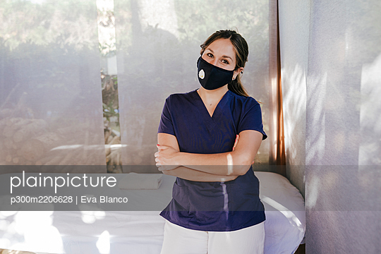 Female therapist wearing mask with arms crossed standing by massage table in spa - p300m2206628 by Eva Blanco