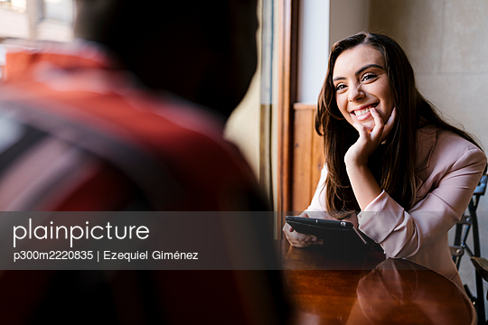 Smiling young woman talking with boyfriend in cafe - p300m2220835 by Ezequiel Giménez