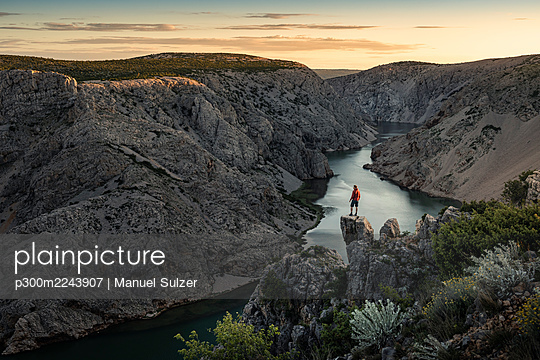 Man standing on rocks and looking at river in canyon at sunset - p300m2243907 by Manuel Sulzer