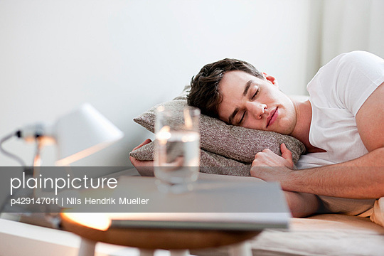 Man asleep in bed - p42914701f by Nils Hendrik Mueller