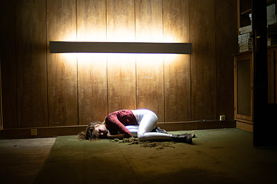 Verzweifelte junge Frau liegt auf dem Fußboden - p1321m2223414 von Gordon Spooner