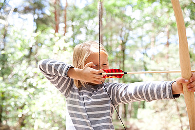 Girl shooting with bow and arrow in the forest - p300m1499630 by Michelle Fraikin